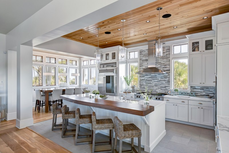 bar style kitchen table shaker cabinets marble countertops matchstick backsplash hardwood floors low back chairs ceiling lights glass pendants stainless steel appliances beach style