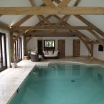 Barn Style Pool Enclosure With Exposed Beams And White Ceilings