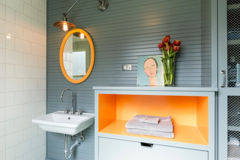 bathroom color trends wall mounted sink round mirror hanging lamp orange shelf white tile grey backsplash contemporary design