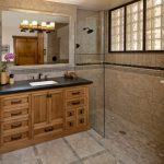 bathroom with walk in shower with limestone flooring, wall, wooden cabinet with granite top, glass partition