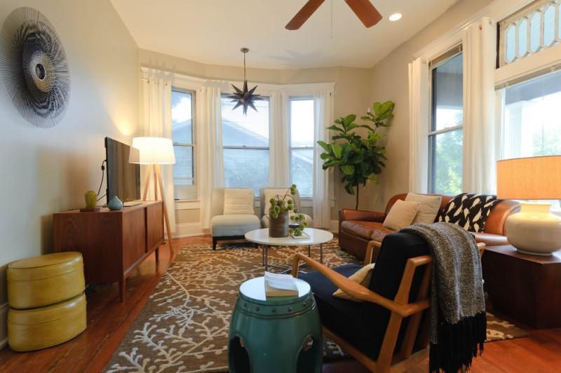 beige walls freestanding tv medium toned wooden floors coffee table rug floor lamp table lamp side tables barrel table