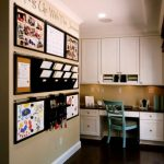 black wall organizer with pinned pictures, calendar, children painting, small shelves