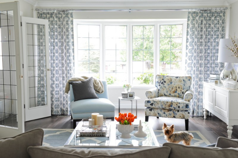 blue accent chairs white and blue curtains glass framed doors and windows rectangular glass coffee table rug wooden floor pillow throw table lamp