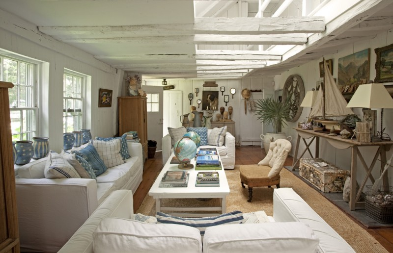 blue antique jars white and blue pillow throws globe mirrors ship art work wall arts deck hardwooden floor rattan rug white coffee table