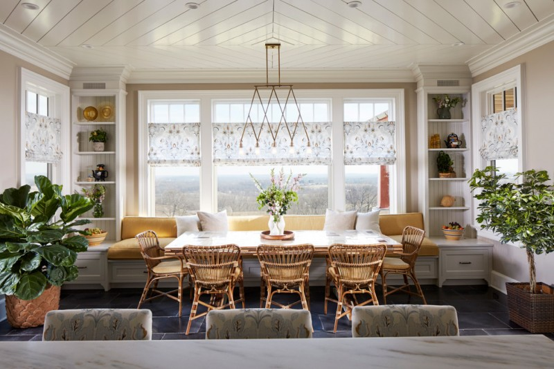 breakfast nook benches low back chairs long dining table marble countertop recessed panel cabinets plant pots chandelier ceramic tiles farmhouse style
