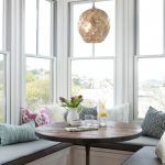 Breakfast Nook Benches Throw Pillows Round Table Flower Centerpiece Vase Glasses Modern Pendants Windows Transitional Design