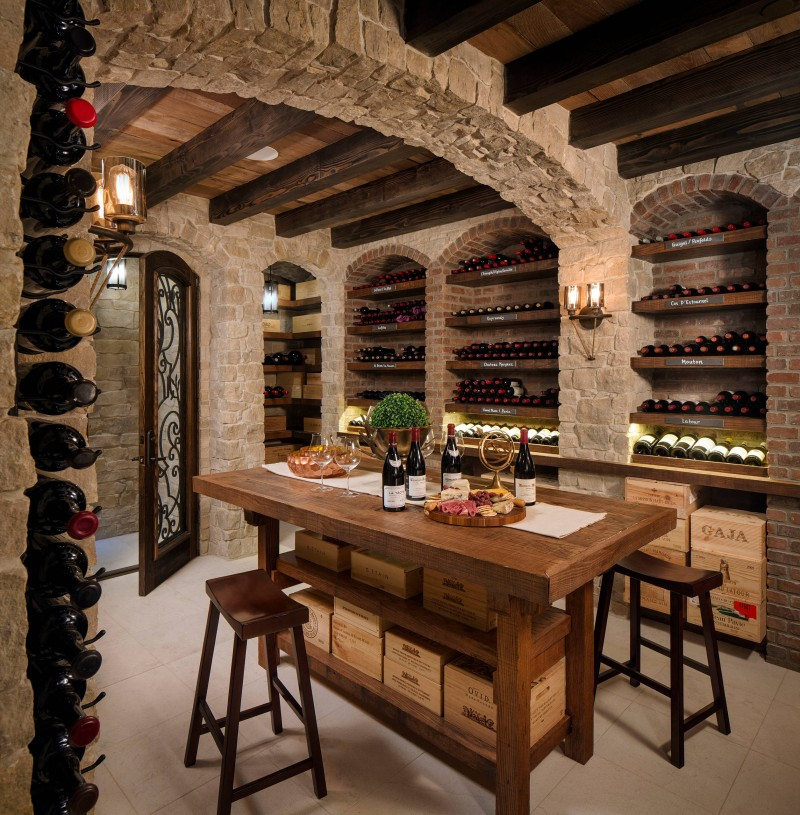 brick wall stone wall wooden beams farmhouse wooden table bar stools tiled floor arched wine storage