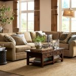 Brown Pottery Barn Pearce Sofa Pillow Throws Wooden Kitcen Table Cream Rug Brown Floor White And Green Vase