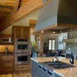 brown yellow granite top kitchen island with six stove under a square cooker hood