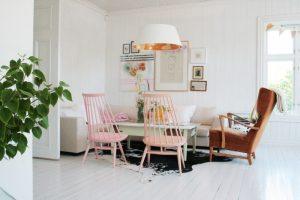 calypso home furniture table tall back chairs couch corner sofa pendant paintings white walls carpet hardwood floors scandinavian design