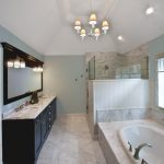 carrera marble bathrooms drop in tub chandelier wall lamps dark wood cabinets white tiles faucets mirror traditional design