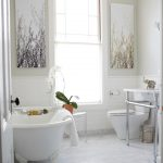 carrera marble bathrooms subway tiles console sink claw foot tub two piece toilet hanging lamp standing towel rack shower wall decoration traditional style
