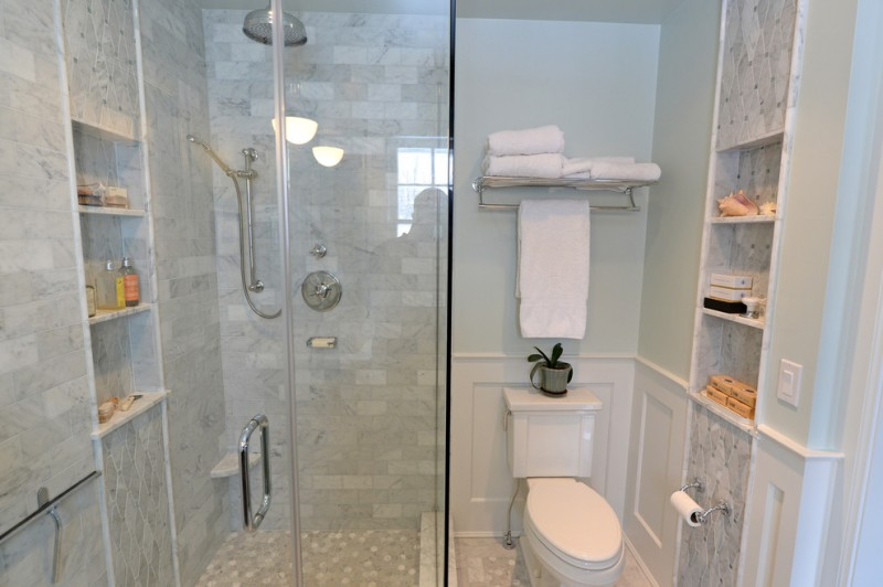 carrera marble bathrooms two piece toilet alcove shower furniture like cabinets hanging towel rack white walls subway tiles traditional design