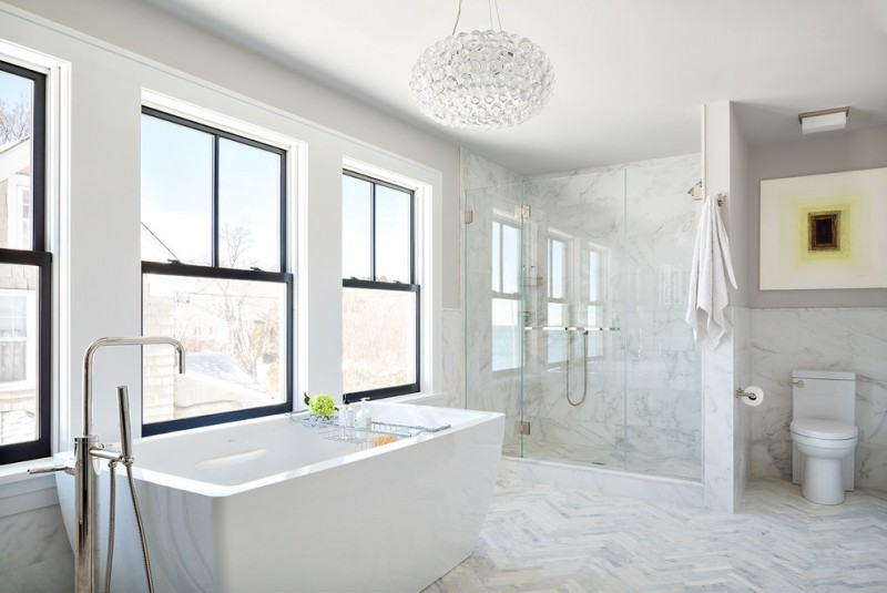 carrera marble bathrooms white tiles ceiling lamp chandelier one piece toilet freestanding tub alcove shower mirror glass door contemporary design