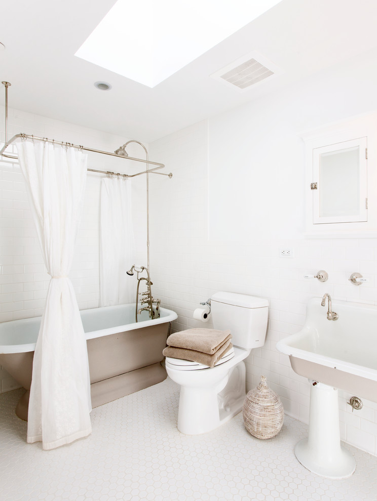clean white traditional bathroom brown base bathtub with white shower curtain and gold toned canopy white toilet white free standing sink white painted concrete walls white ceramic floors