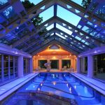 Clear Glass Pool Enclosure With Glowing Blue And Low Lighted Yellow Lighting Fixtures