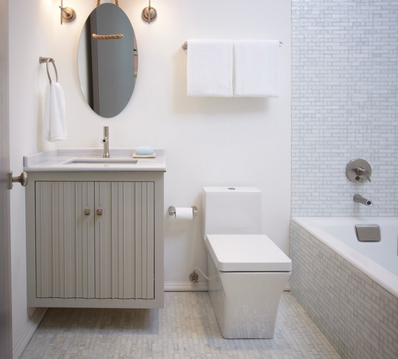 coastal bathroom idea small size mosaic ceramic tiles walls & floors white concrete walls modern white toiler grey floating vanity with undermount sink frameless oval mirror
