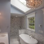 Coastal Bathroom Idea With Marble Tiles Walls And Floors Blue Walls Marble Countertop With Two Undermount Sinks Crystal Pendant Lamps Free Standing Bathtub In White Mid Size Skylight