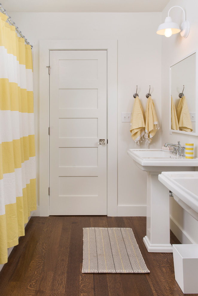contemporary bathroom with white pedestal sink frameless mirror dark toned wood floors white walls yellow white stripes shower curtain