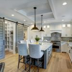 Contemporary & Coastal Kitchen Idea White Cabinets Supported With Black Metal Handles Stainless Steel Appliances Grey Bricks Backsplash Light Blue Kitchen Island With Storage White Worktop And Chairs