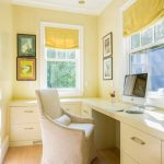 Cozy And Warm Study Room With L Shape Built In Computer Desk White Chair Slipcover Light Toned Hardwood Floors Light Yellow Walls Accented By Bright Yellow Window Curtains