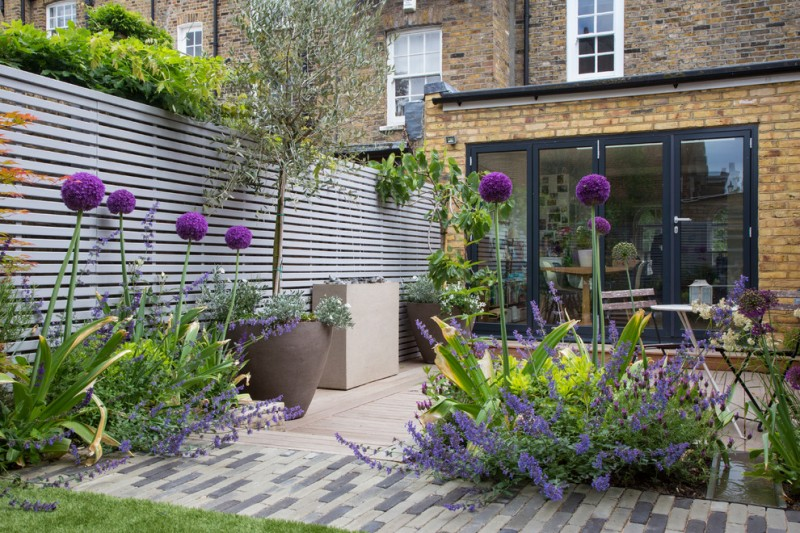 decking wall small rectangular black and tiles floor big pots lavender flowerds glass door brick walls