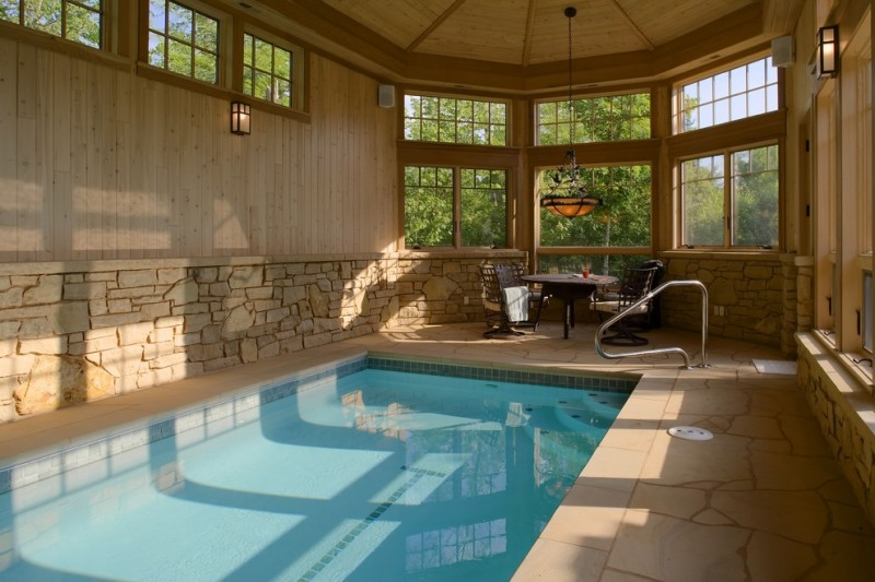 eclectic pool enclosure for lake house rectangular indoor pool halfway wood siding walls halfway natural stones walls unfinished wood ceilings