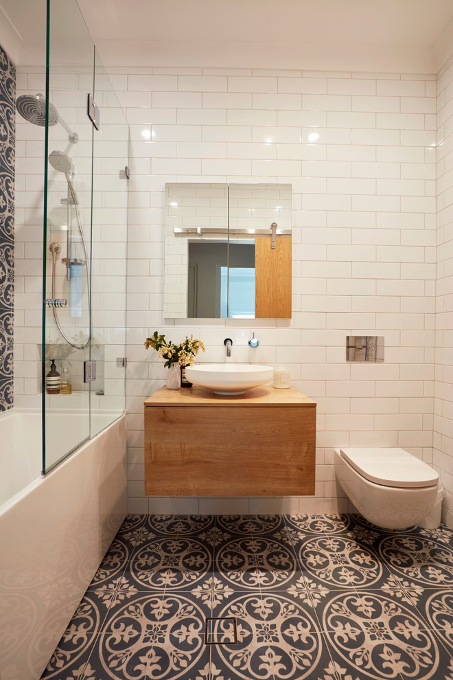 family bathroom white subway tiles walls ceramic tiles floors with traditional patterns floating wood vanity with white vessel sink frameless mirror a recessed cabinet wall mounted toilet