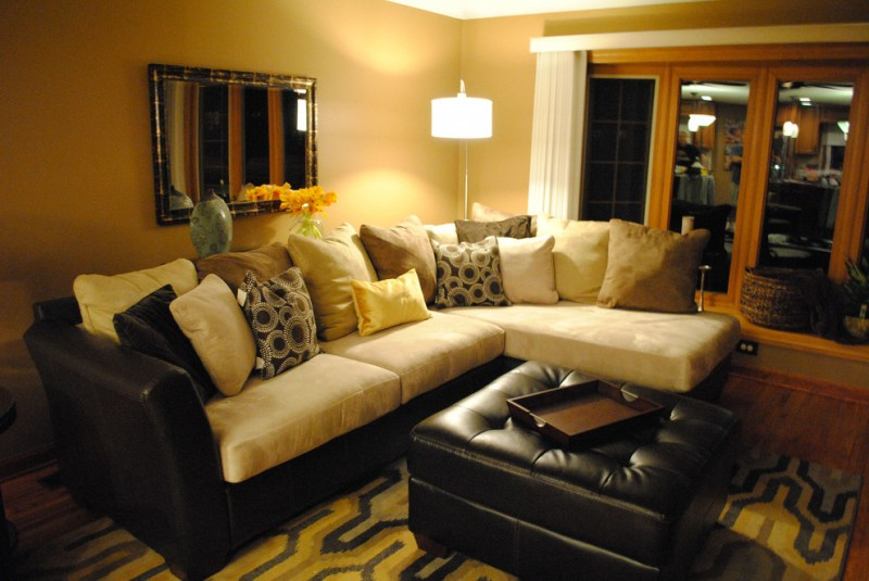 family room with insufficient lighting light yellow walls idea L shape black couch with light yellow seater black leather center table medium toned wood floors decorative mirror with gold toned frame