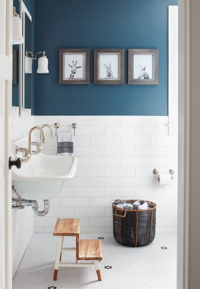 farmhouse bathroom idea with navy blue walls white subway tiles walls wall mounted sink small wood staircases black basket for storage white mosaic tiles floors