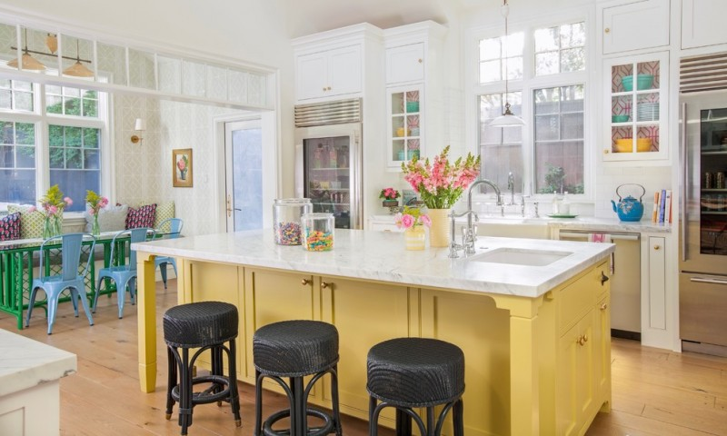 farmhouse kitchen idea with playful colors application white top kitchen island with yellow cabinets and black stools