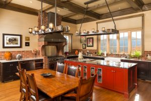 farmhouse kitchen model with red kitchen island attached with shaker cabinets and black marble worktop wood dining furniture set  medium toned wood floors red bricks walls