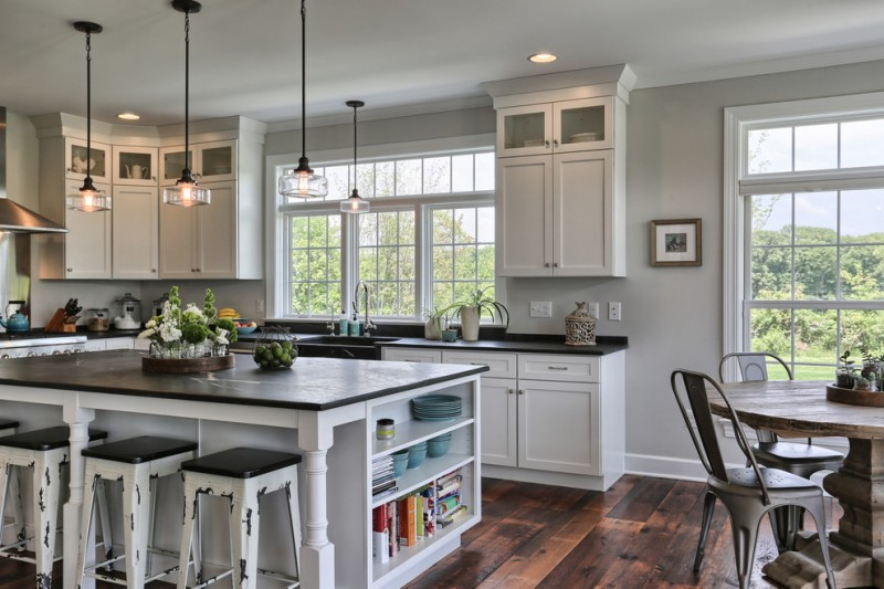 farmhouse kitchen remodel with black countertop white cabinets black top kitchen island with side open shelves and black white bar stools dark wood slabs floors