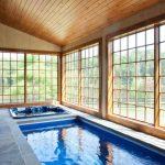 Farmhouse Pool Enclosure Idea Natural Stone Floors Rectangular Indoor Pool Small Spa Pool Wood Stained Ceiling Indoor Pool Light Fixtures