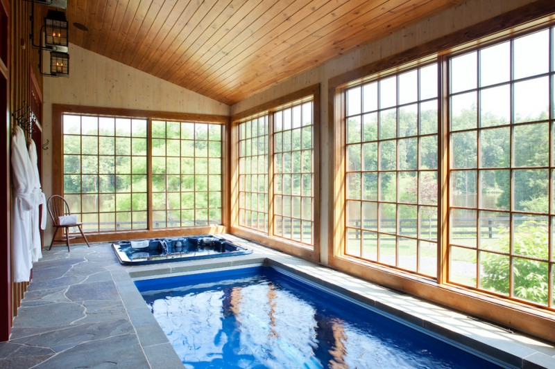 farmhouse pool enclosure idea natural stone floors rectangular indoor pool small spa pool wood stained ceiling indoor pool light fixtures