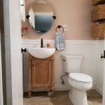 Frameless & Oval Vanity Mirror Single Wood Cabinet White Undermount Sink And Black Wrought Iron Faucet White Toilet Classic Vanity Lamp Vertical Arranged Box Storage Light Pink And White Wall