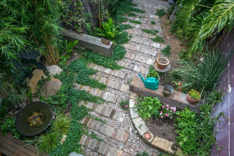 garden seat water tank concrete pavers small colorful pebbles bamboo plants bushes pots