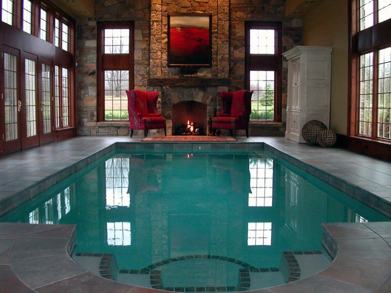interior pool with dark natural stones fireplace and walls two grand red chairs a contemporary artwork pale natural stone floors white closet storage