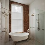 jacuzzi tub shower combo brick wall glass claw foot bathtub racks glass shelf ceiling light industrial bathroom