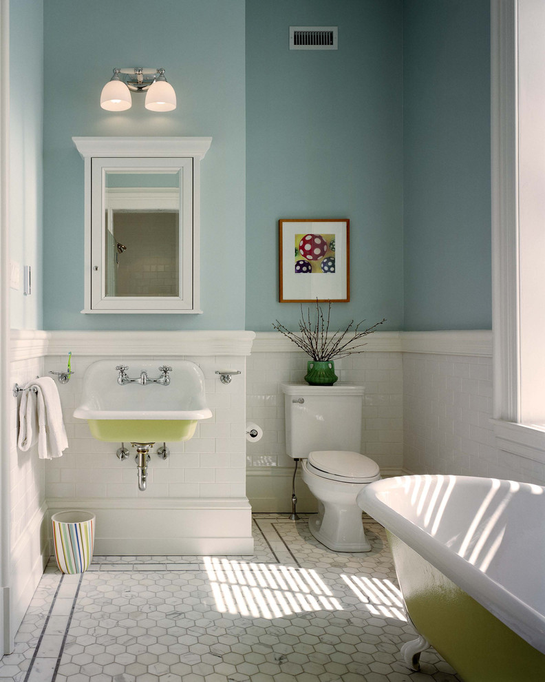 light blue concrete walls white ceramic base walls two piece toilet in white wall mounted sink with green base wall mount storage with mirror front white ceramic floors claw foot tub