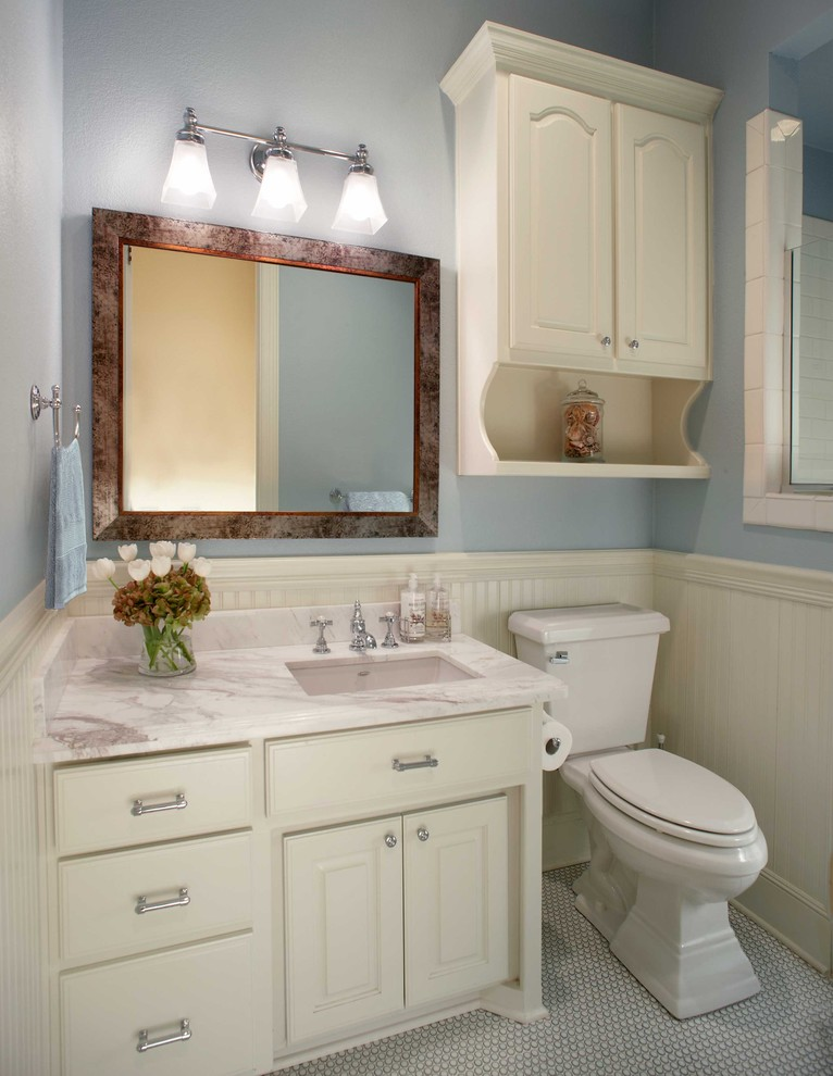 light blue walls accented by textured white base white bathroom vanity two piece toilet in white mid sized mirror with dark frames white marble countertop small ceramic floors in white