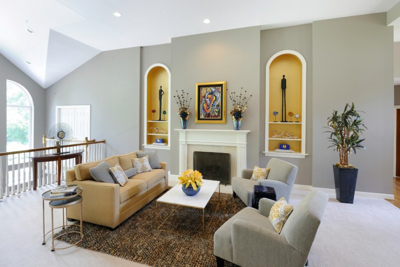 light grey walls with recessed yellow shelving units yellow and grey couches with colorful accent pillows multicolored area rug modern side table white mantel fireplace white floors