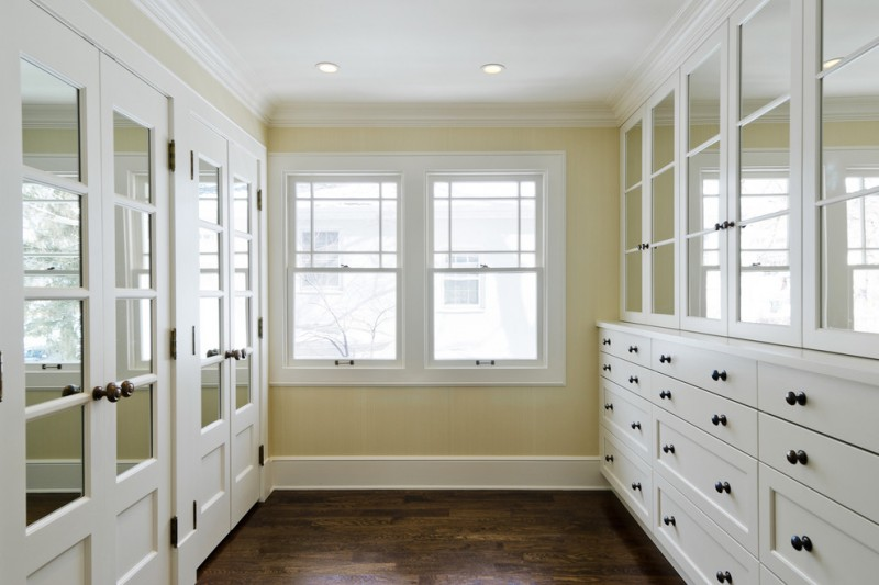 master closet room mirrored closet doors glass front cabinets and white cabinets Built in drawers medium toned wooden floor cream wall