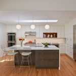 Mid Century Kitchen Clean White And Flat Panel Kitchen Cabinets Stainless Steel Appliances White Top Kitchen Island With Dark Wood Cabinets Medium Toned Wood Planks Floors Modern White Bar Stools