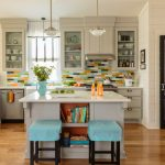 Mid Sized Kitchen Island With Book Shelves And A Couple Of Striking Blue Chairs L Shape Kitchen In White With Colorful Tiles Backsplash White Countertop And Stainless Steel Appliances