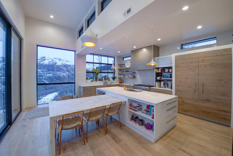 minimalist kitchen white minimalist kitchen island included with open shelves flat panel cabinetry and undermount sink light wood floors light wood dining tables with chairs L shape & white counterto
