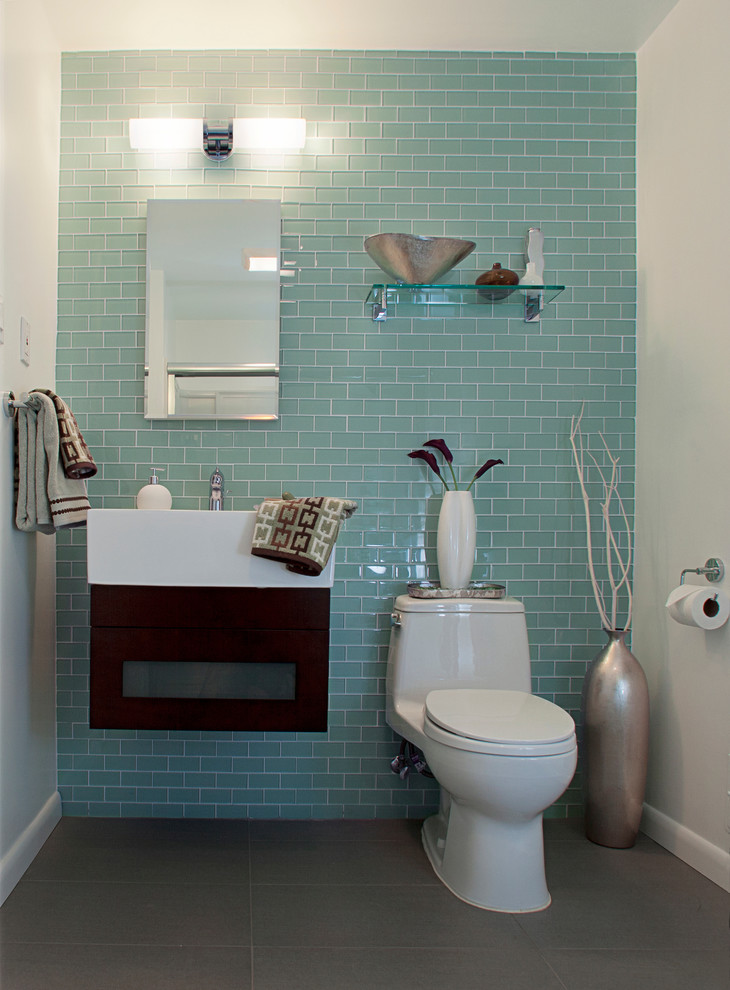 modern guest bathroom with blue subway ceramic wall white concrete walls Ronbow vanity two piece tilet frameless mirror wall mounted glass shelf grey ceramic floors