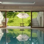 Modern Interior Pool With White Concrete Enclosure Tile Floorings Sliding Glass Door And Large Skylight