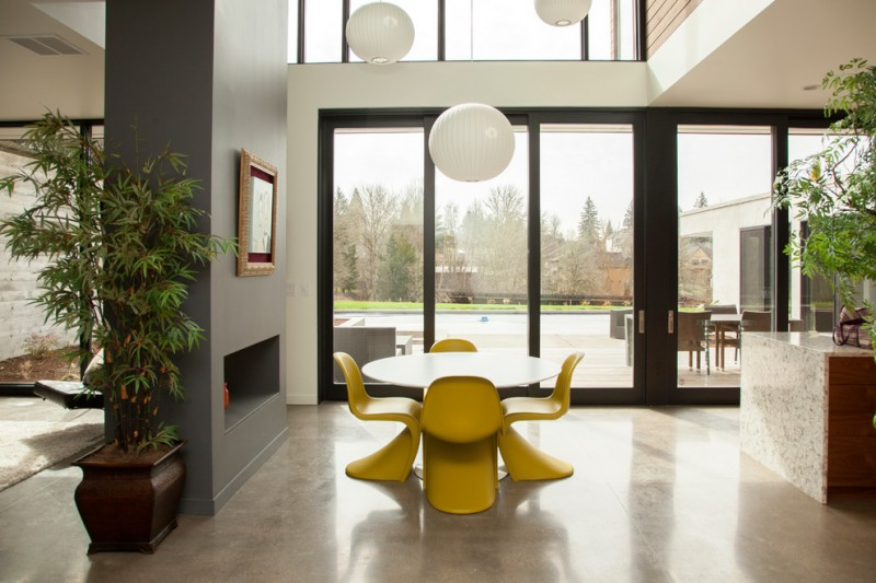 modern minimalist dining room yellow dining chairs round top dining table modern fireplace grey marble floors white walls