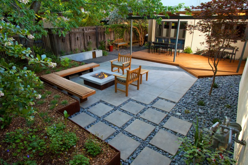 modern patio concrete slab with a lightly washed sand finish pebbles concrete fireplace corner wooden bench dining kitchen set